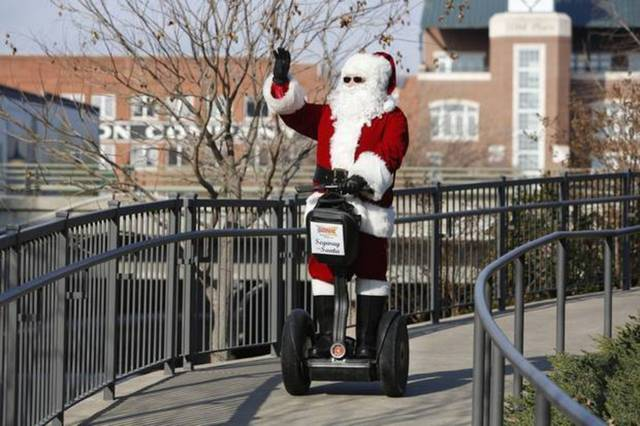 The Sonic Segway Santa, played by Ricky Smith, waves to visitors in Bricktown in Oklahoma City, Friday December 13, 2013. Photo By Steve Gooch, The Oklahoman