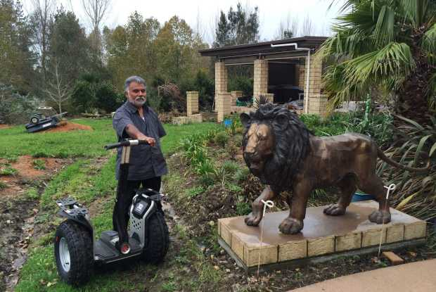 Rohit and his Segway x2, along with one of his two lions that guard his home